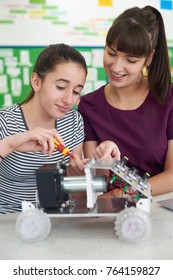 Teacher Talking To Female Pupil Studying Robotics In Science Lesson