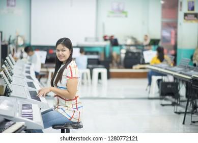 Teacher teach keyboard electone instument to a boy in class room