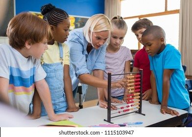Teacher teaching children math on abacus. Mature mathematics teacher helping schoolchildren use wooden abacus. Group of multiethnic kids understanding maths in classroom.