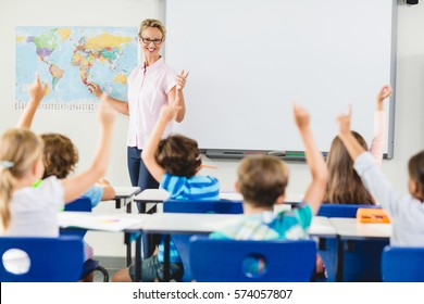Teacher teaching kids in classroom at school