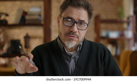 Teacher teaching online from home. Man wearing eyeglasses talking on conference call, explaining in E learning online class, lesson, training course. Mature, middle age, mid adult in 50s.