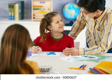 Teacher teaching painting to elementary age children in classroom at primary school.