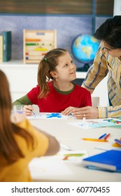 Teacher teaching painting to elementary age children in classroom at primary school.?