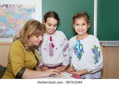 The teacher tells the little schoolgirl  in embroidered
