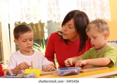 teacher and two preschoolers playing with wooden blocks