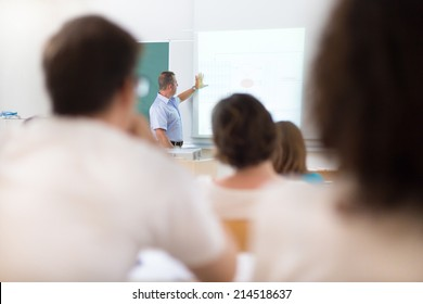 Teacher at university in front of a whiteboard screen. Students listening to lecture and making notes.