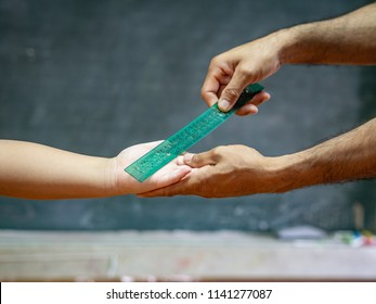 teacher use the ruler hit the kid's hand for punishment.