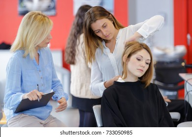 teacher watching trainee hairdresser