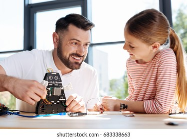 Teacher waving hello to student with robots hand