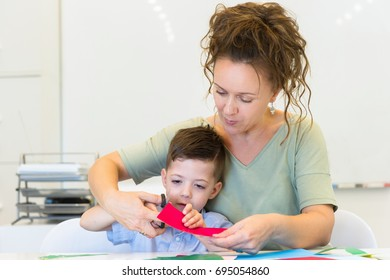 teacher woman and child boy cutting collage color paper with scissors in the classroom