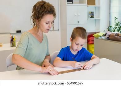 teacher woman learn to use ruler to preschooler boy in the classroom