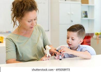 teacher woman playing with child boy with finger puppets in the classroom