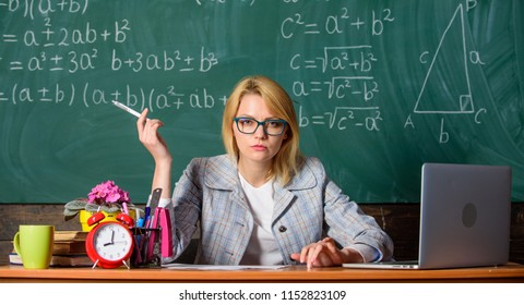 Teacher woman sit table classroom chalkboard background. Create and distribute educational content. Present lesson in comprehensive manner to facilitate learning. Promoting interactive learning.