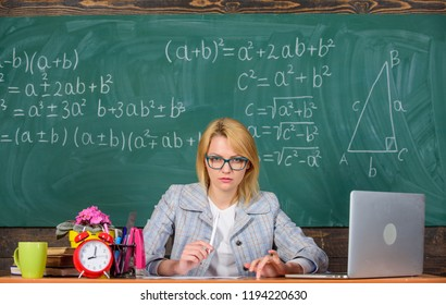Teacher woman sit table classroom chalkboard background. Create and distribute educational content. Promoting interactive learning. Present lesson in comprehensive manner to facilitate learning.