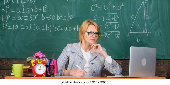 Teacher woman sit table classroom chalkboard background. Present lesson in comprehensive manner to facilitate learning. Promoting interactive learning. Create and distribute educational content.