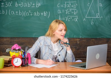 Teacher woman sit table work laptop surfing internet chalkboard background. Present lesson in comprehensive manner use visual to facilitate learning. Organize class and make learning easy process.