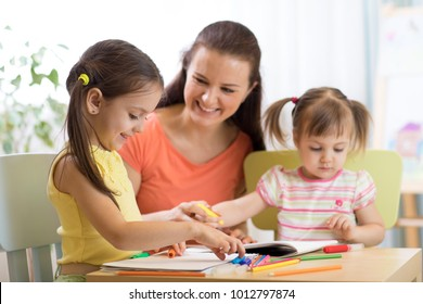 Teacher working with children kids in preschool classroom