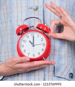 Teachers attributes. Alarm clock in hands of teacher or educator classroom background. School discipline concept. Schedule and regime. Right on time ok gesture. Alarm clock in female hands close up.