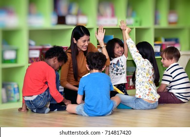 Teachers and children  having fun on learning  in an international school library.teacher ,education, kid and primary school concept .