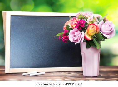 Teacher's day background.Black chalk board frame empty copy space and fresh flowers in vase.Holiday feminine  poster.Spring greeting 8 march icon.