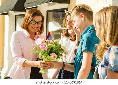Teacher's Day, outdoor portrait of happy middle aged female high school teacher with bouquet of flowers and group students