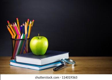 Lehrertisch mit Farbstift, Notizbuch und anderen Geräten.