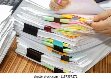 Teacher's hand is checking student homework assignment and report on desk in office for score. Unfinished paperwork stacked in archive with color papers and paper clips. Education and business concept