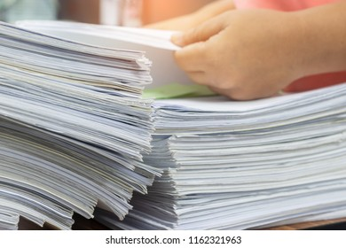 Teacher's hands are searching for student's homework assignments on table in office to make a check and inspect. Stack of unfinished paperwork and reports. Education and business concept.