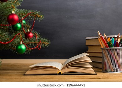 Teacher's table with books, organizer and chalkboard. The concept of Christmas and New Year.