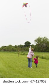 Teaching a child to fly a kite on a dreary day parenting and guidance concept
