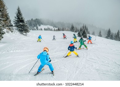 Teaching children skiing. Child skiing in the mountains with instructor. Children learning ski on the slope. mountain ski resort. winter sport.  Kid in ski school. Winter sport for kids. Making turns