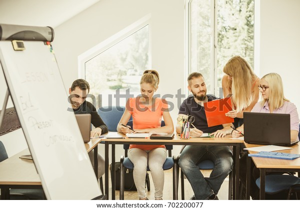Teaching Concept. Female young teacher or tutor with adult students in classroom with papers, laptop computer. Studies course