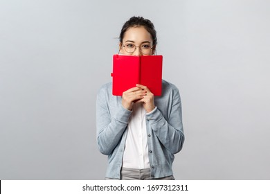 Teaching, education and university lifestyle concept. Silly blushing asian girl hiding her face behind diary, holding notebook or planner, hiding something she wrote from people, smiling with eyes