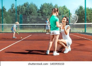 Teaching girl. Dark-haired loving caring mommy smiling while teaching girl playing tennis