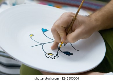 Teaching painting on handmade decorative ceramic plate, man's hand paints a bright floral pattern with a brush, Petrykivka painting style