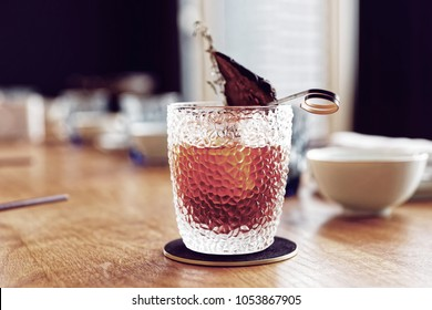 Tea-colored cocktail with dried pear, Asian style drink, toned image