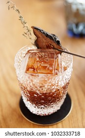 Tea-colored cocktail with dried pear and thyme