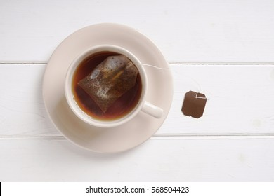 teacup with black tea teabag left to draw in cup