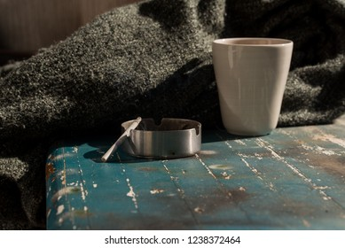 Teacup, blanket and ashtray grey fall background