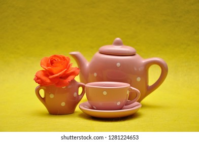 A teacup and a kettle with an orange rose on a yellow background