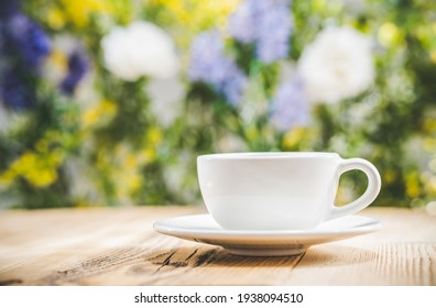 Teacup on wooden table in front of blurred nature background of flovers and leaves. Bokeh concept - selective focus. White tea cup. Blank free space for your advertising or text. Copyspace