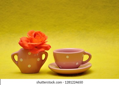 A teacup with an orange rose on a yellow background