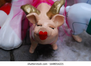 teacup pig figurine with red lipstick lips  and closed eyes, looking up