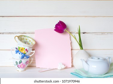 Teacups Stacked with a White Teapot, a Purple Tulip, and Light Pink Invite Card on Table and Against White Board Background with room or space for copy, text, your words. A horizontal with side view