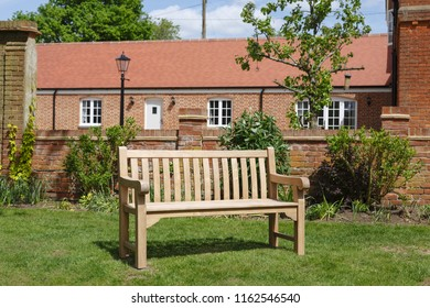 Teak hardwood bench on a lawn in an English garden with historic Victorian home in the background