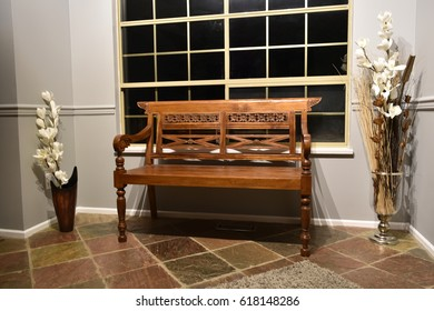 A teak wood bench by a window at night.