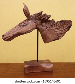 teak wooden horse face on a metal stand