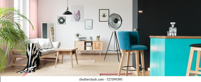 Teal bar stools in a living room standing behind a black wall in an interior housing modern furniture like a stylish sofa or a coffee table