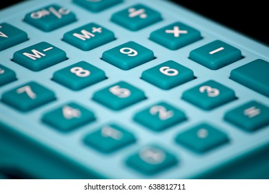 A teal blue calculator with a shallow depth of field ready to get your budget on track
