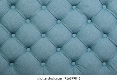 Teal blue capitone textile background, retro Chesterfield style checkered soft tufted fabric furniture decoration with buttons, close up